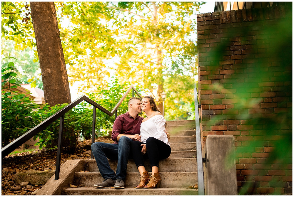 man and woman sit and laugh outside of vernon alden library for engagement session