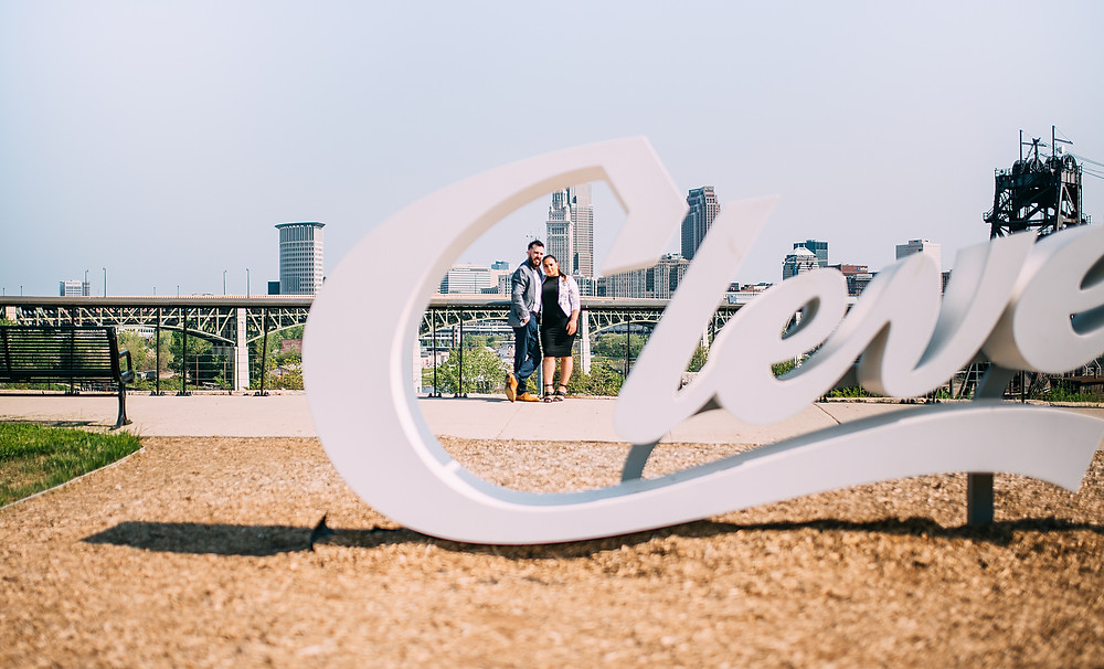 """Man and woman portrait through the Cleveland """"C"""" sign"""