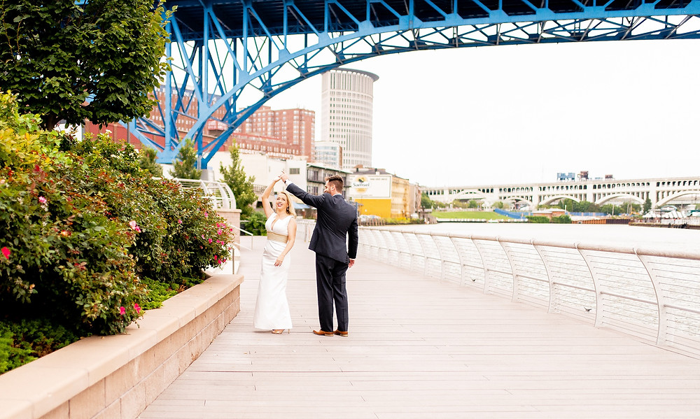 bride and groom stand in settler's landing park in the flats of cleveland ohio