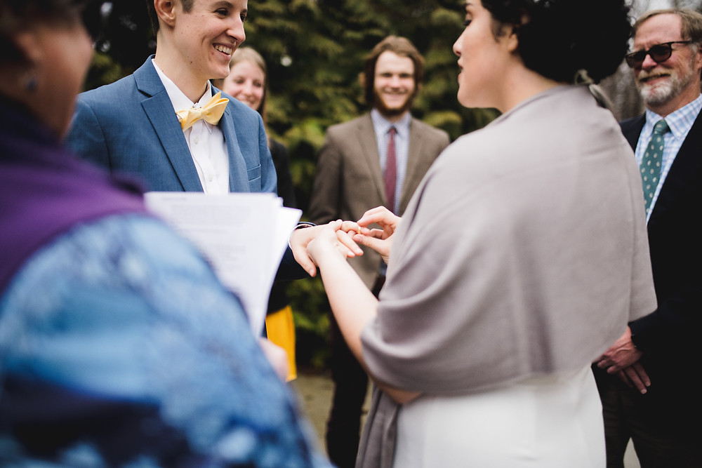 Bride smiles and puts ring on other bride's finger