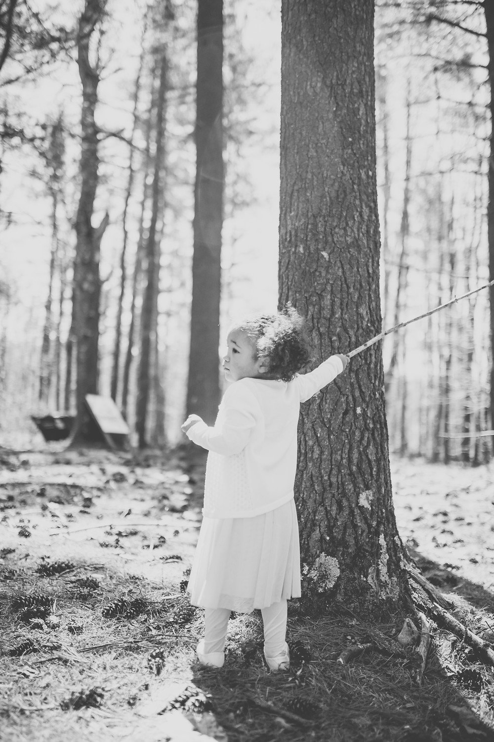 Little girl playing with a stick in the woods