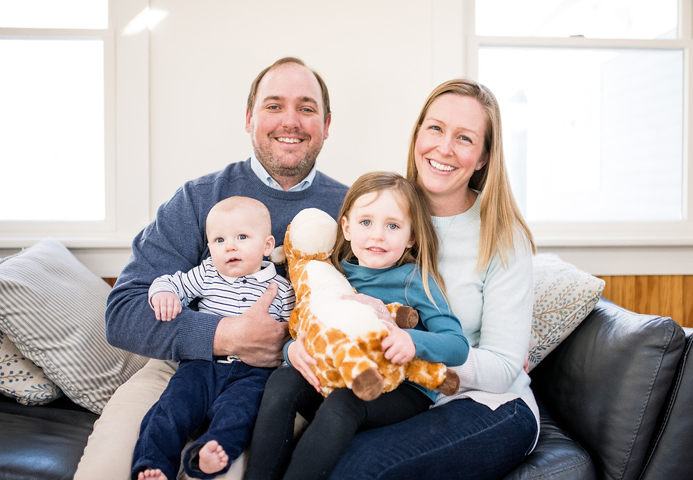 smiling family sits on the couch together with plush toy giraffe