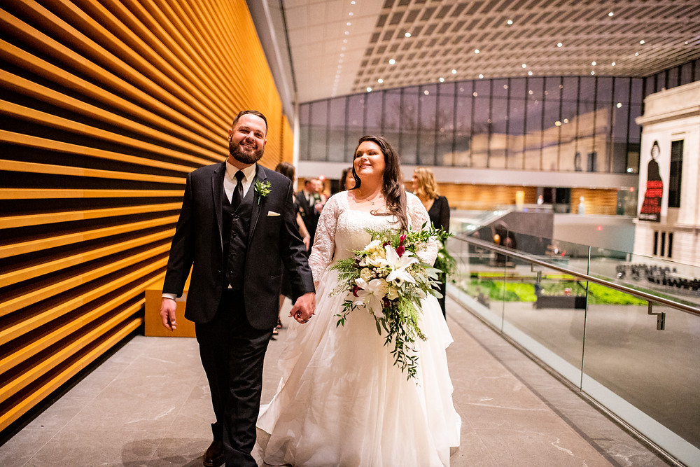 bride and groom smiles and walk together during wedding at the cleveland museum of art