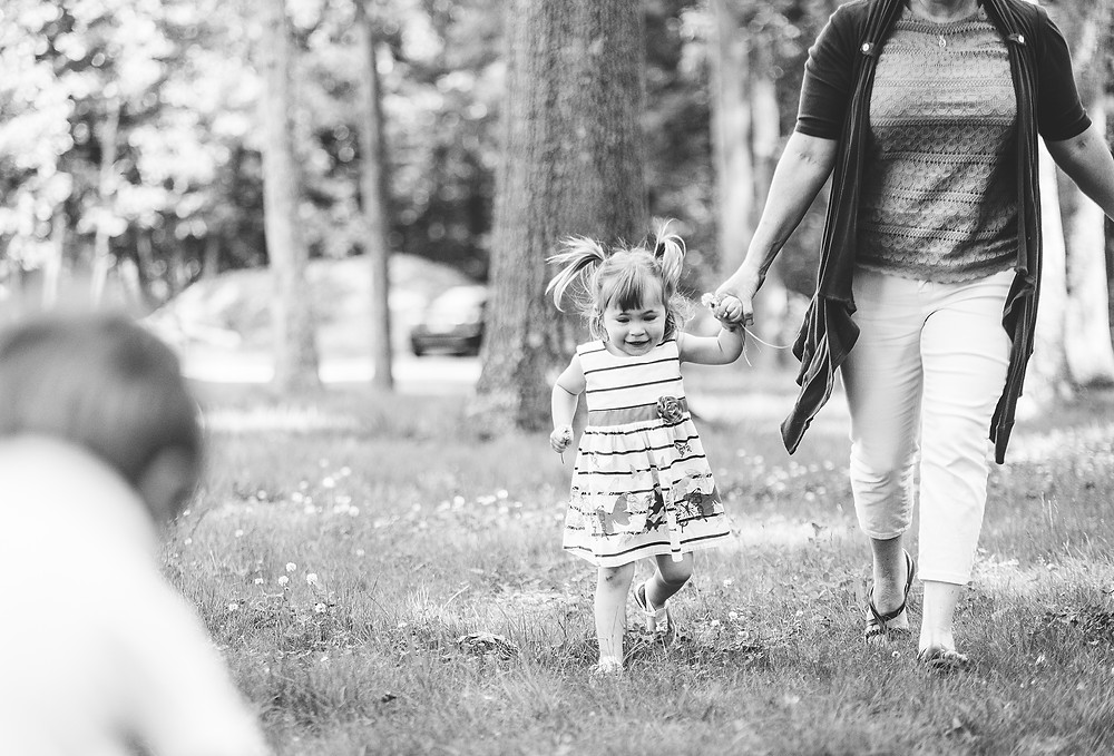 Little girl and mom run through grass and have lots of fun.