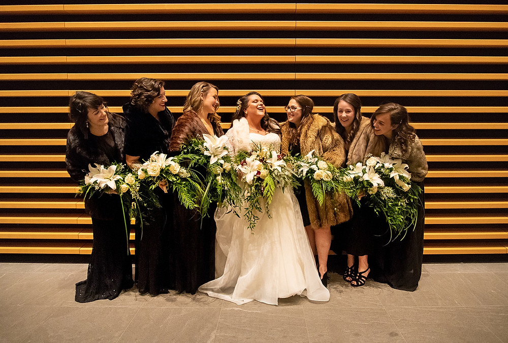 bride and bridesmaids laugh and smile during wedding at the cleveland museum of art