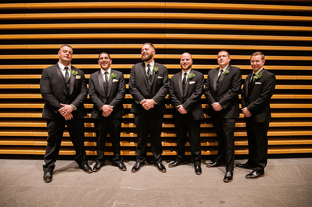 groomsmen laugh and smile at the cleveland museum of art