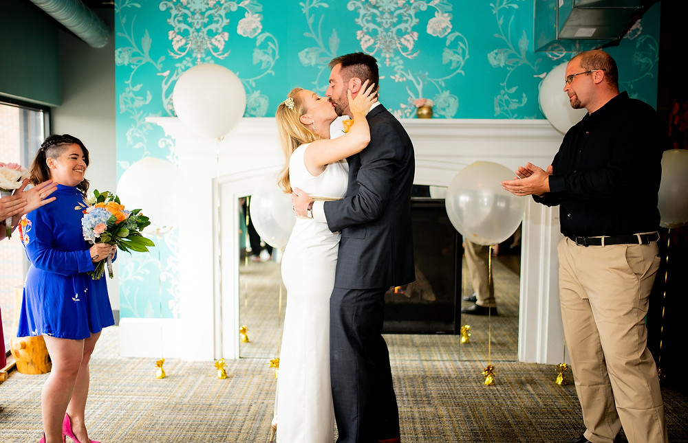 bride and groom kiss during wedding ceremony at punch bowl social, cleveland ohio
