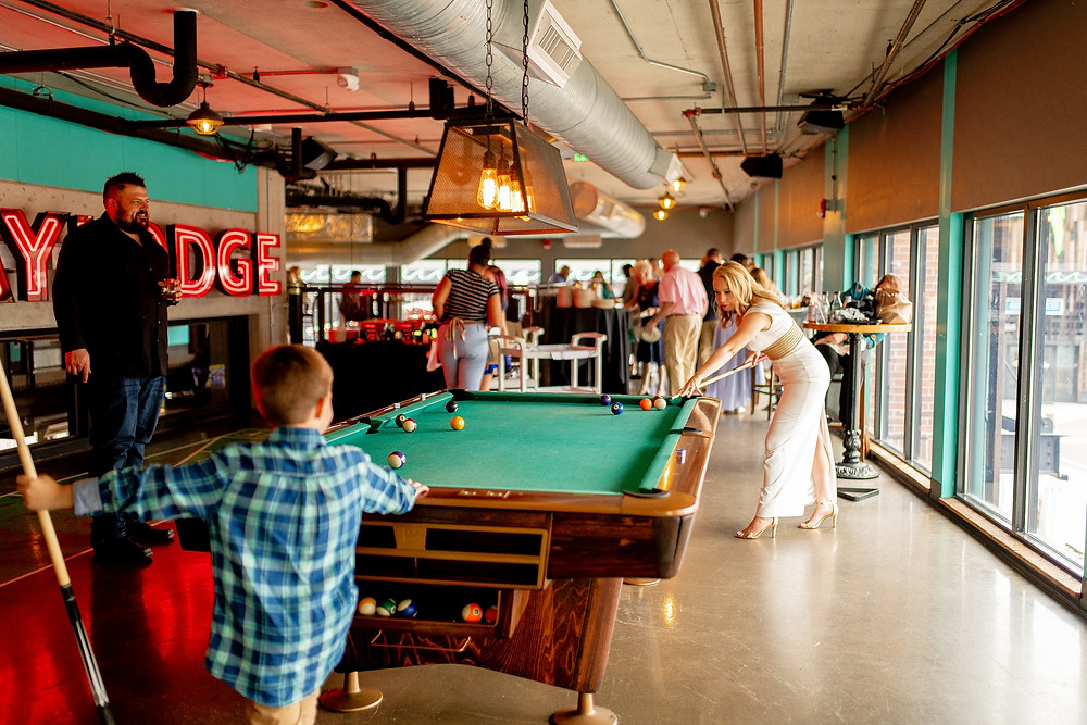 bride plays pool in wedding dress at punch bowl social in the flats of cleveland ohio