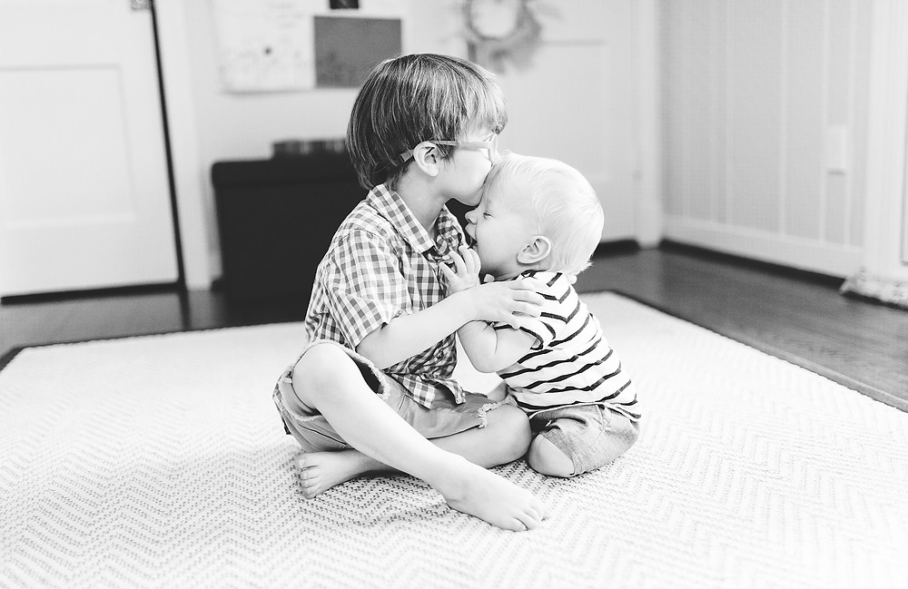 Two little boys hug and kiss on a carpeted floor