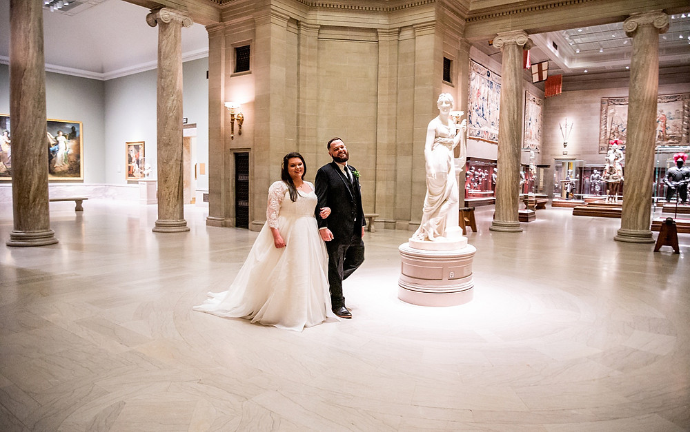 bride and groom hold hands and walk through cleveland museum of art gallery