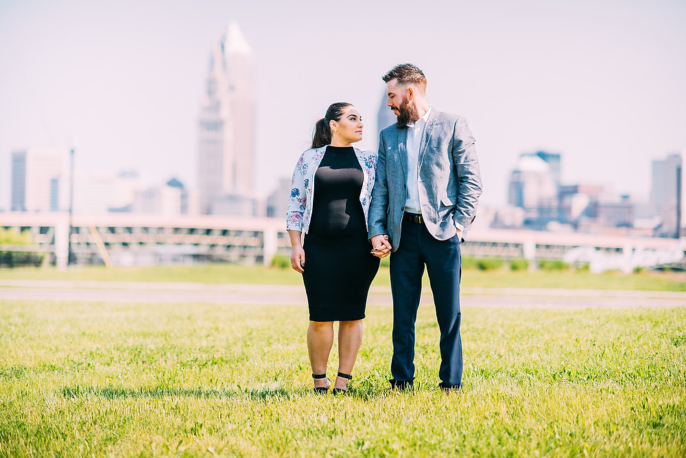 Man and woman stand and look at one another with the city skyline in the background