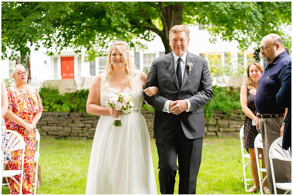 bride and father walk down the aisle during the processional