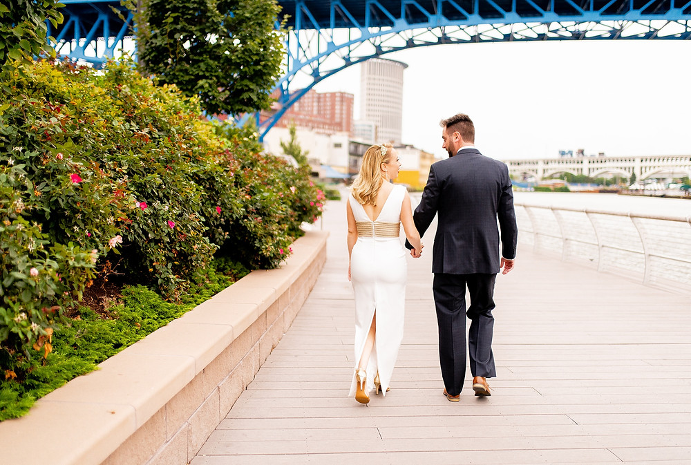 bride and groom stand in settler's landing park in the flats of cleveland ohio next to cuyahoga river