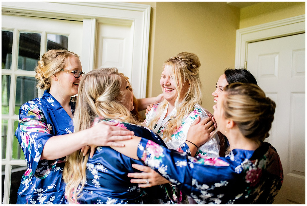 bride and bridesmaids hug and laugh together
