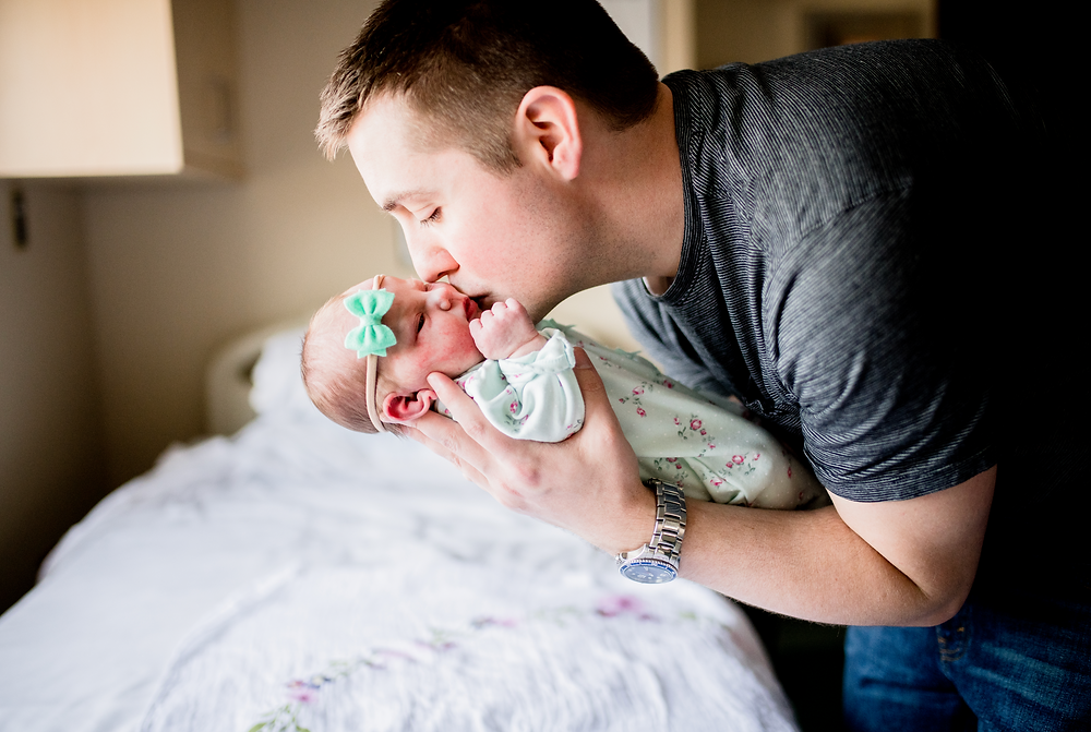 dad hugging and kissing newborn baby in the sunlight