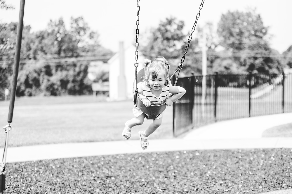 Little girl swings and smiles as she has fun on the swing set