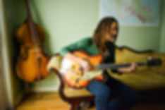 female musician sitting on a vintage couch and playing guitar