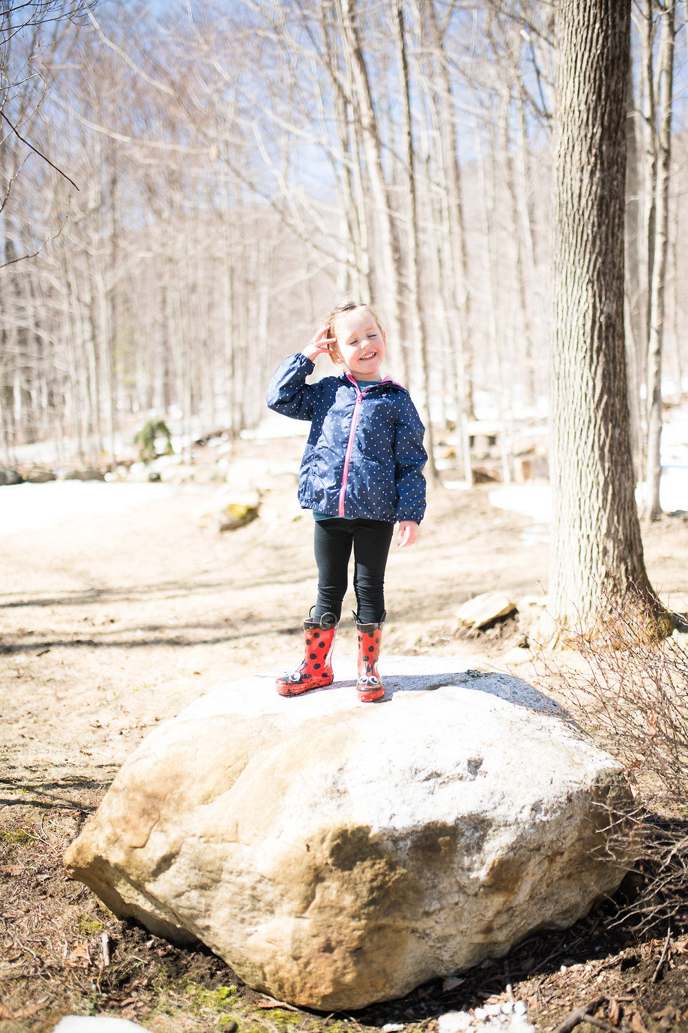 little girl stands proudly on a rock in the sun