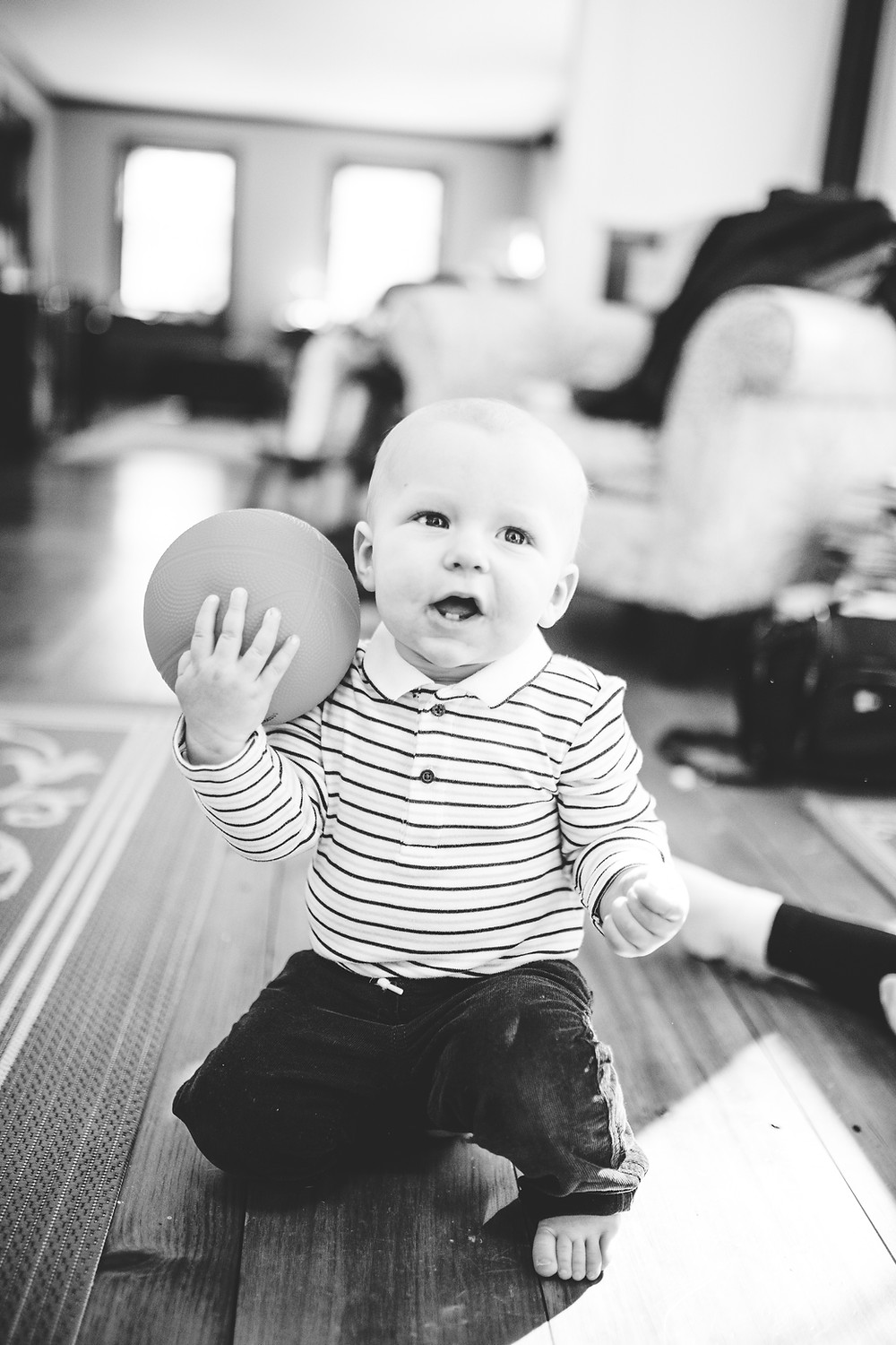 little boy holds his favorite basketball and shows his two front teeth