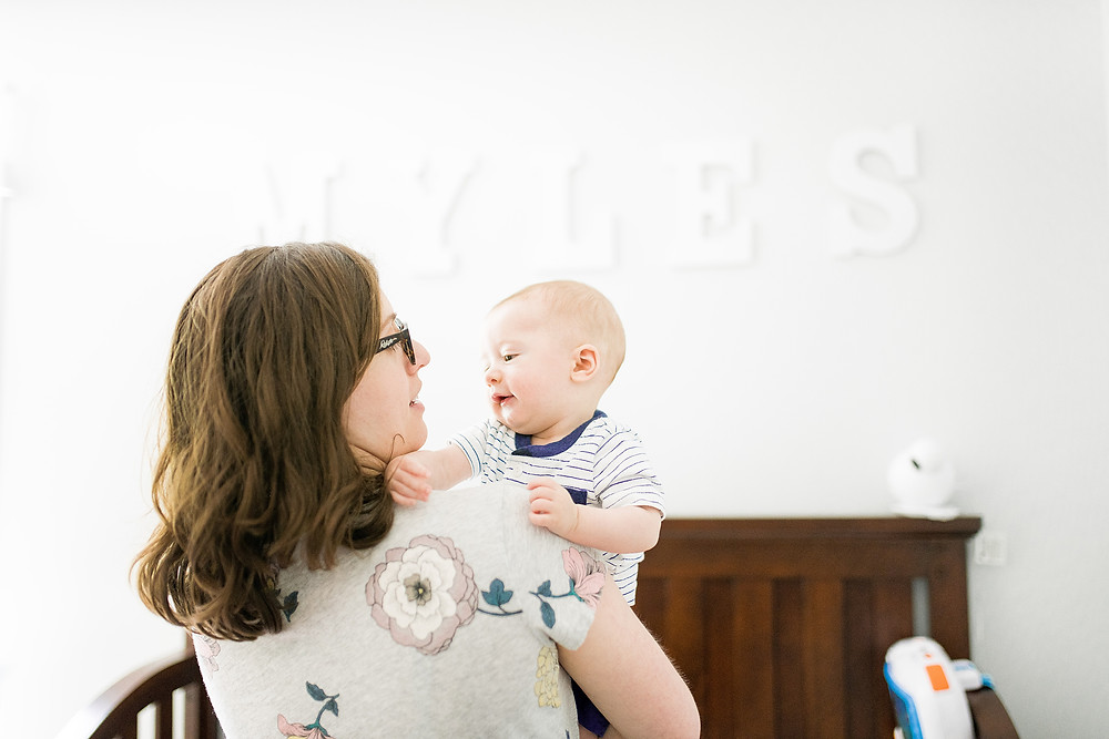 Mom and baby play in his nursery during the daylight