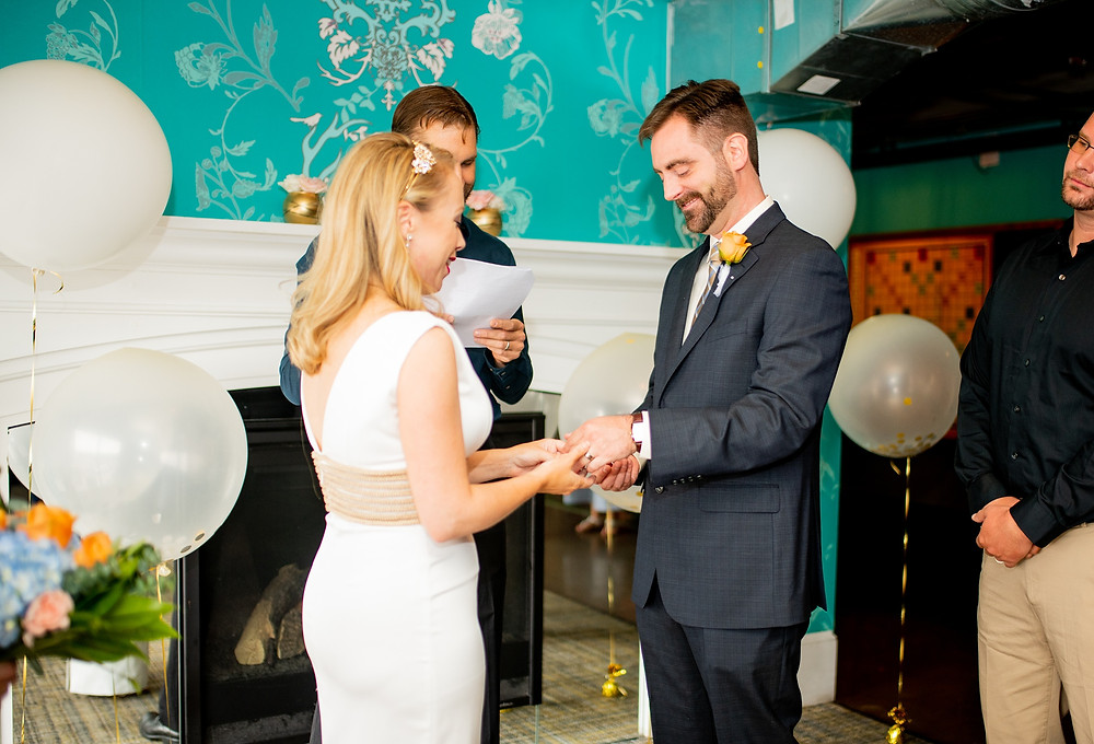 groom puts ring on bride's finger at punch bowl social cleveland ohio
