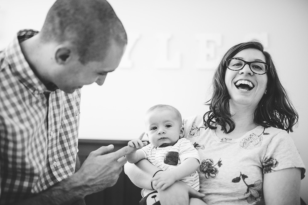 Mom and dad hold baby in nursery and play with his fingers