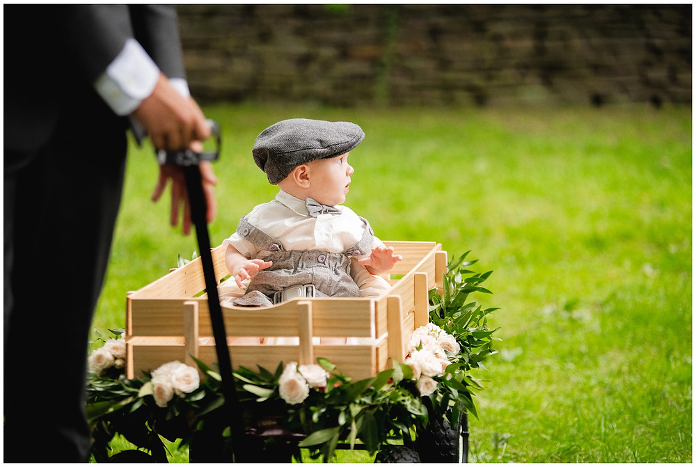 little ring bearer rides in a wagon down the aisle