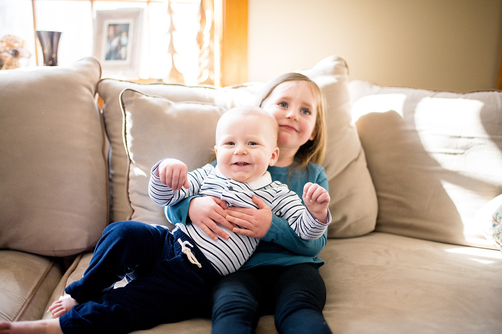 small girl holds her baby brother who is smiling on the couch