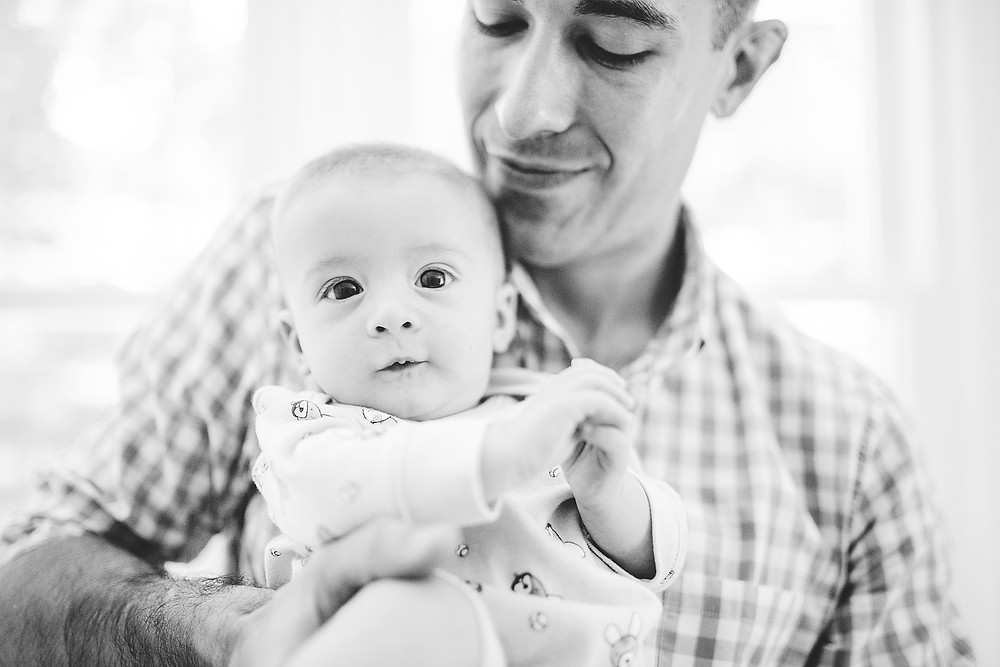 Dad holds baby and smiles as baby makes a curious face
