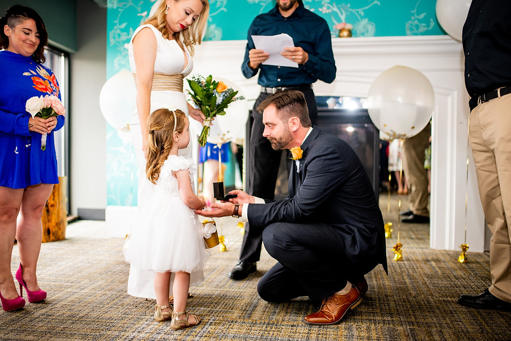 groom gives flower girl a present during wedding ceremony in cleveland ohio