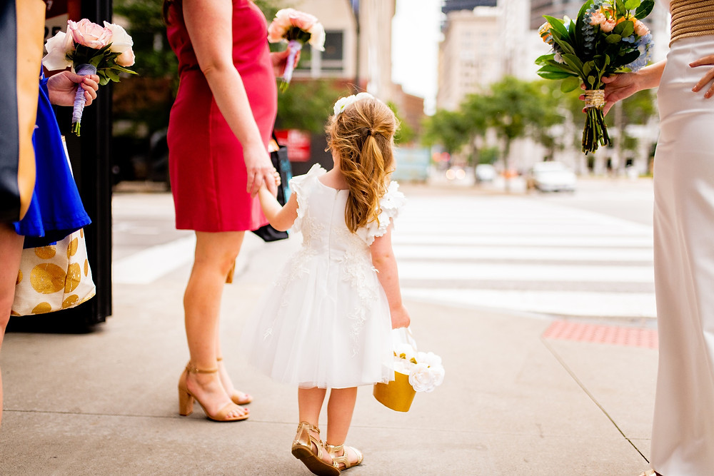 flower girl holds hands before crossing the street in cleveland wedding