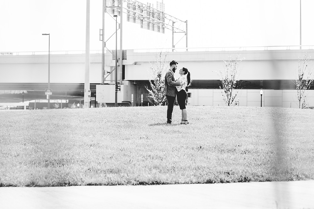 Man and woman stand with one another on a grassy hill in Cleveland