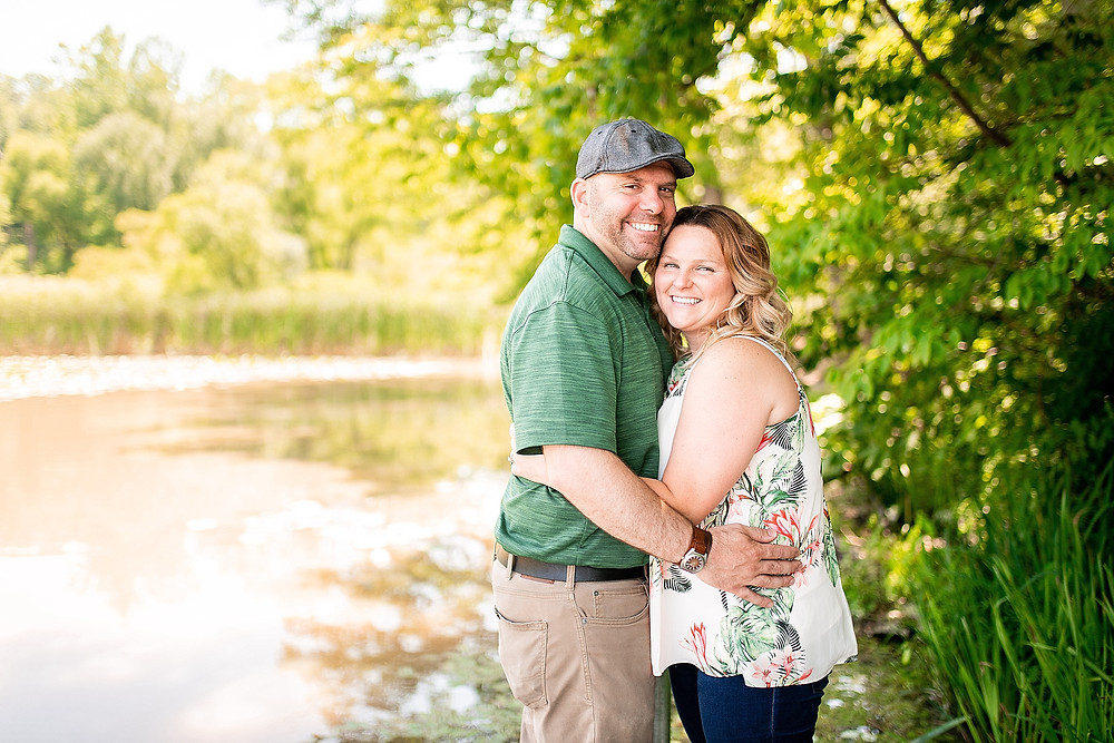 Man and woman hug and smile during engagement session at Hinckley Reservation