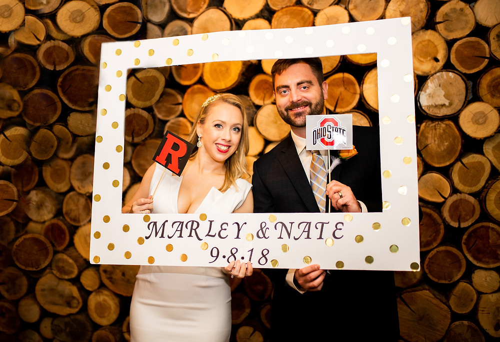 bride and groom take a photo in selfie station at punch bowl social during wedding reception in the flats of clevleand ohio