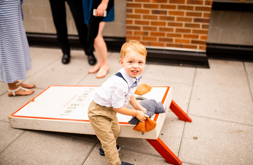 little boy playing cornhole at punch bowl social at wedding in the flats of cleveland ohio