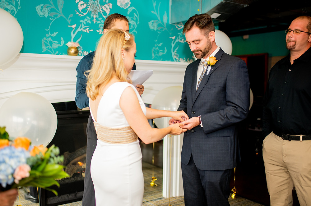 groom receives ring from bride during ceremony at punch bowl social the flats cleveland ohio