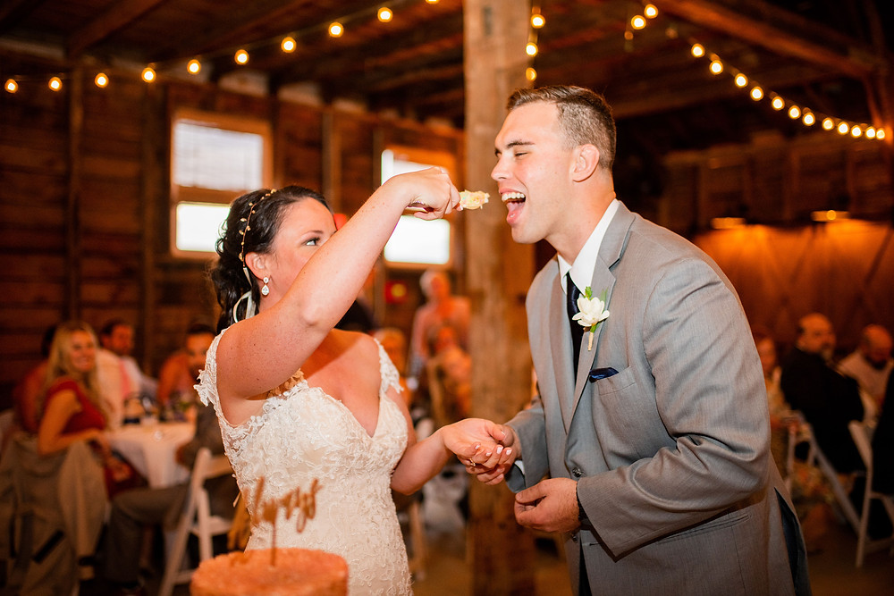 bride feeds cake to groom during reception at hillcrest fun farm in northeast Ohio