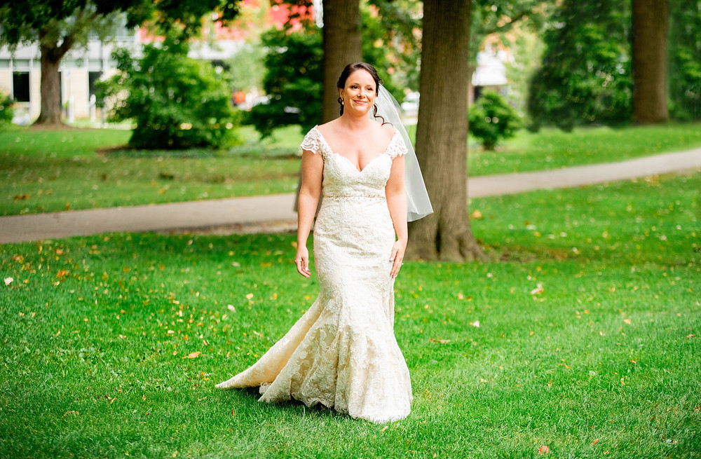 Bride walks across the campus at Oberlin College during the first-look