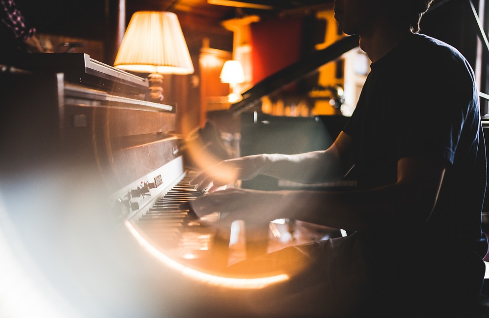 light ring around pianist's hands playing keyboard