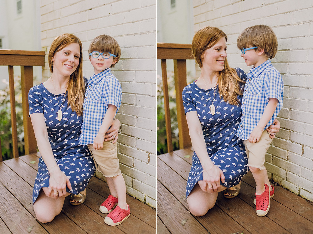A woman in a blue dress holds her son close who is wearing a blue plaid shirt