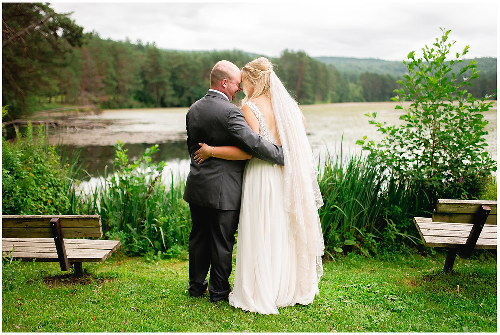 bride and groom kiss in front of lake in vermont