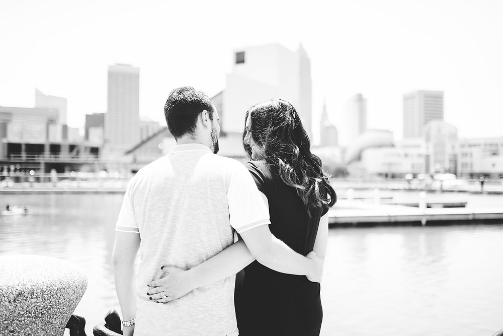 Black and white engagement featuring a man and woman by the Cleveland skyline