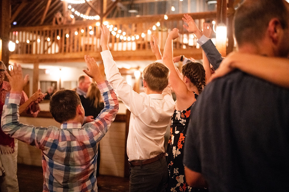 guests cheer and hold their hands up during horah