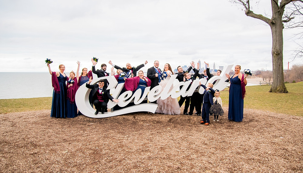 bride and groom and wedding party cheer at edgewater park in cleveland ohio