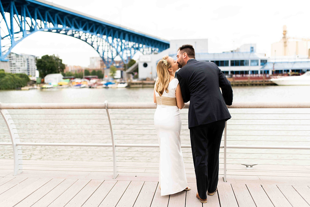 bride and groom kiss next to the cuyahoga river and main avenue bridge in the flats, cleveland ohio