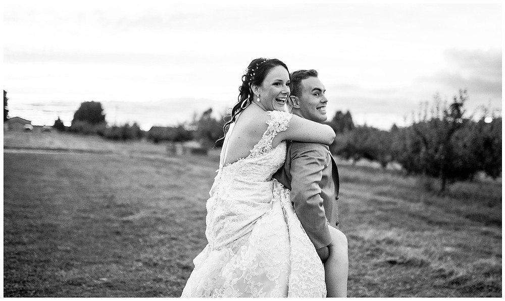 groom gives bride a piggy back ride during reception at hillcrest fun farm near amherst Ohio