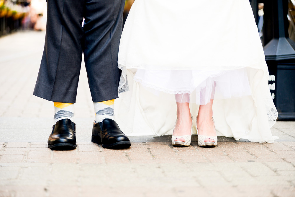 Bride and groom socks and shoes as they stand on East 4th Street