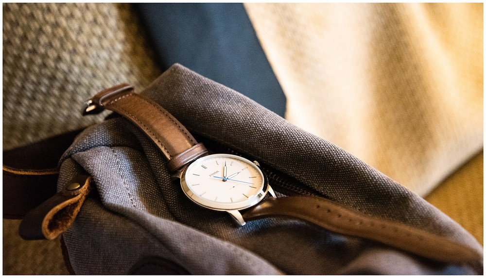 grooms gift of a watch on top of his clothing