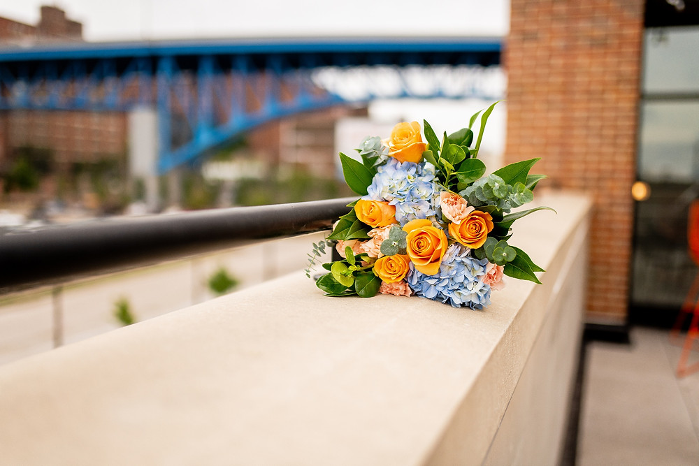 bridal bouquet on rooftop of punch bowl social overlooking the main avenue bridge in cleveland ohio