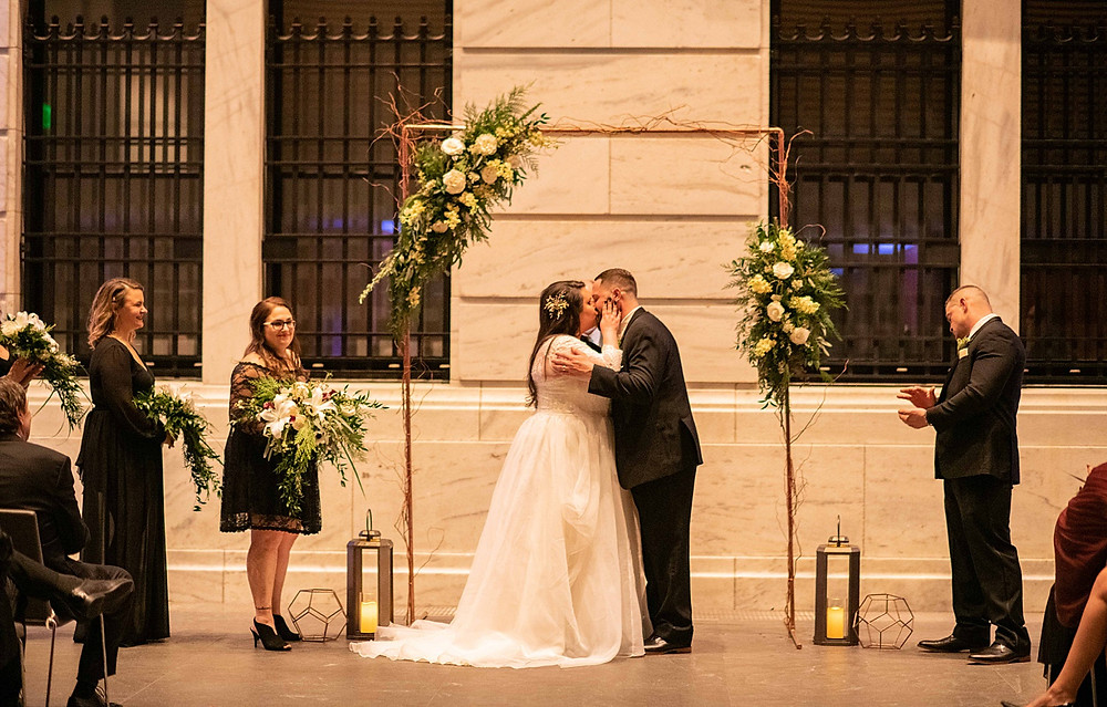 bride and groom share their first kiss under the arch at the cleveland museum of art